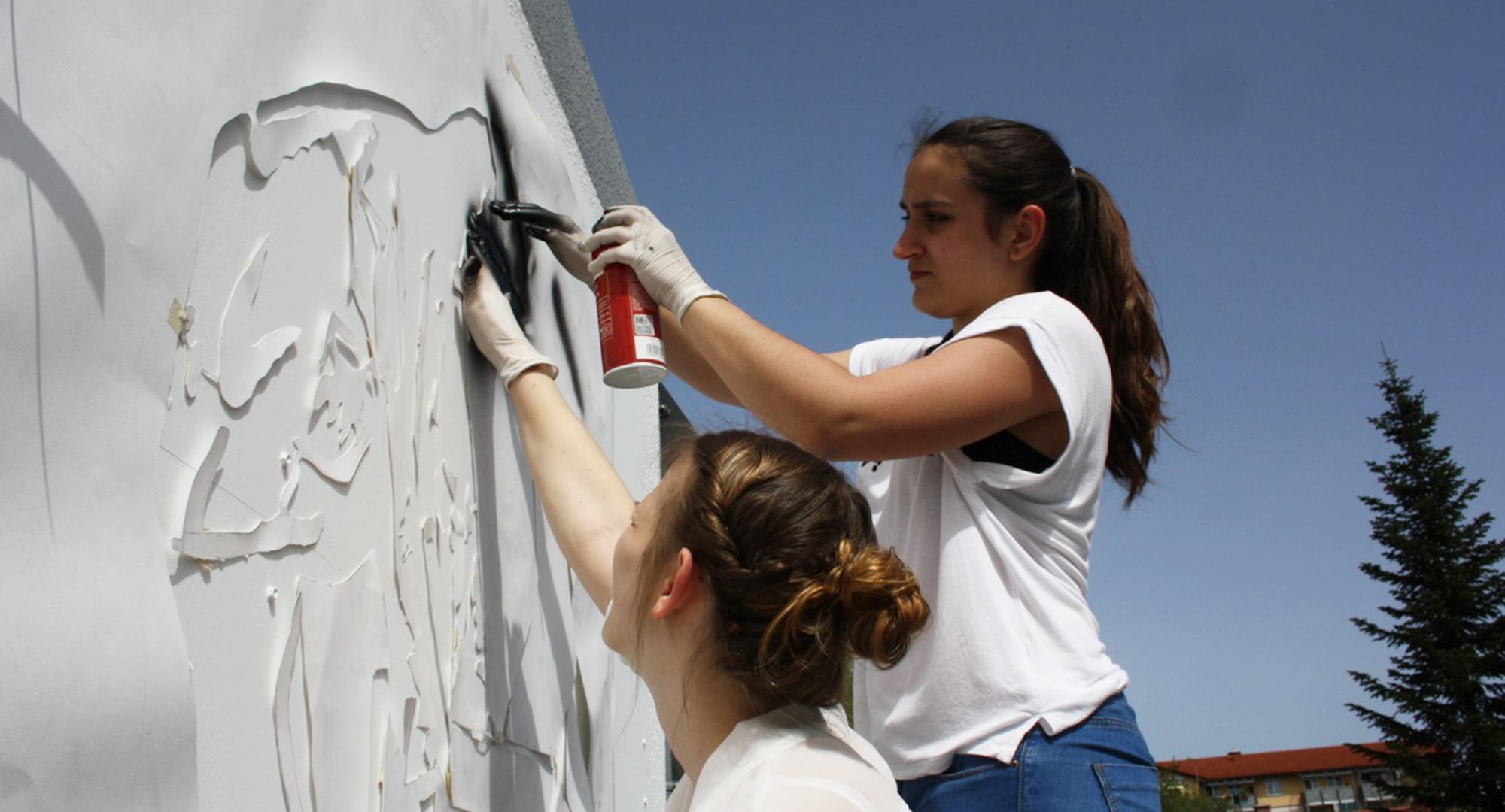 Detailaufnahme der schülerinnen beim Sprayen der Kunstwerke an die Rothmoser Trafohäuser
