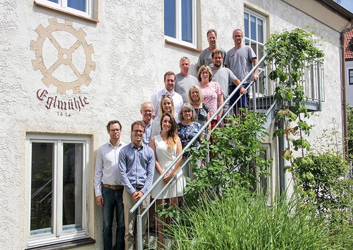 Rothmoser Teamfoto alle Mitarbeiter vor Geschäftshaus am Urtelbach
