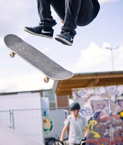 Skatepark Bild, Junge beim Sprung mit Skateboard
