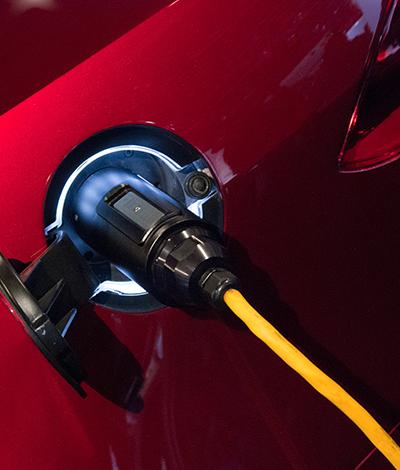 Detailbild von eienem Elektroauto Tankdeckel bei dem das gelbe Kabel eingesteckt ist