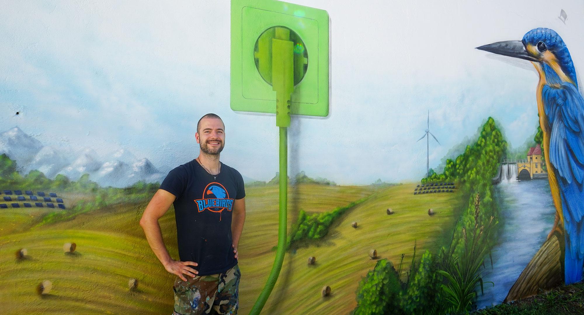 Detailsfoto von Pyser vor dem Graffiti für Rothmoser zum Thema Nachhaltigkeit mit einem Eisvogel, der Natur rund um Grafing und einer großen grünen Steckdose als Symbol für dne Rothmoser Naturstrom